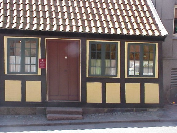 H.C. Andersens barndomshjem Munkemøllestræde i Odense. Familien Andersen boede ved de to vinduer til højre og havde fælles indgang og forstue med Familien Köcker. der boede til venstre.